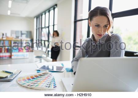 Designerin mit Laptop neben Farbfelder in office - Stockfoto