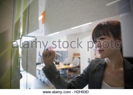 Zeichnen auf Glas im Büro Geschäftsfrau - Stockfoto