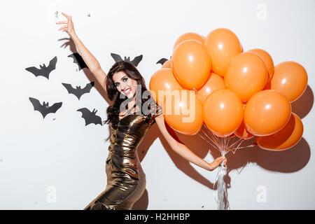 Fröhliche junge Frau mit erschrecken Vampir Schminke und Haufen orange Luftballons Spaß auf weißem Hintergrund - Stockfoto