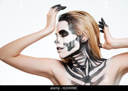 Frau mit Angst vor Halloween Make-up stehen und posiert auf weißem Hintergrund - Stockfoto