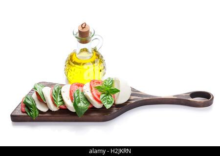 Caprese-Salat. Mozzarella, Tomaten und Basilikum auf Schneidebrett. Isoliert auf weißem Hintergrund - Stockfoto