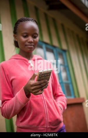 Eine junge Frau ist ihr Mobiltelefon in Kirinyaga County, Kenia tätig. - Stockfoto