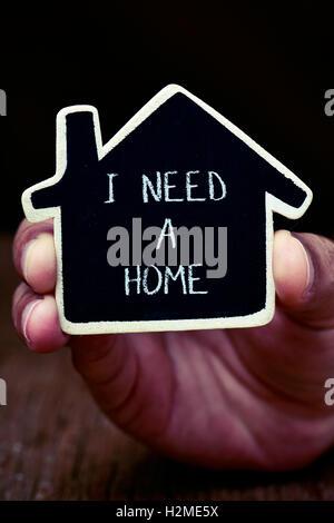 Nahaufnahme der Hand eines jungen Mannes zeigt ein schwarzes Haus-förmigen Schild mit dem Text brauche ich ein Haus - Stockfoto