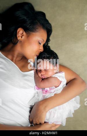 Eine afrikanische amerikanische Mutter legt auf ihrer Seite ihre neugeborene Tochter hielt.  Sie küsst sie auf die - Stockfoto