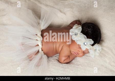 Eine friedliche afroamerikanische neugeborenes Mädchen schläft süß mit einem Tutu und ein florales Stirnband.  Von - Stockfoto
