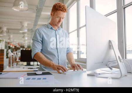 Aufnahme des jungen Mannes an seinem Schreibtisch stehen und arbeiten am Computer. Geschäftsmann, arbeiten in modernen - Stockfoto
