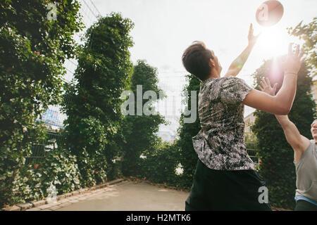 Freunde, Basketball gegeneinander spielen und Spaß am Außenpool. Zwei junge Männer Basketball zu spielen, an einem Sommertag. Stockfoto