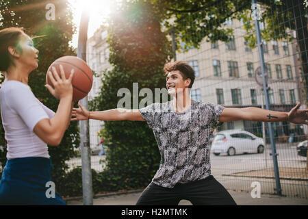 Zwei junge Mann und Frau Streetball gegeneinander ausspielen. Teenager Freunden eine Partie Basketball auf einen - Stockfoto