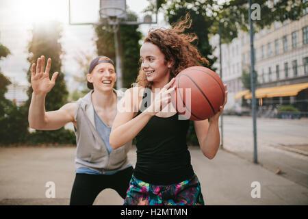 Junges Mädchen Basketball spielen, mit jungen zu blockieren. Teenager Freunden eine Partie Streetball auf Freiplatz. - Stockfoto