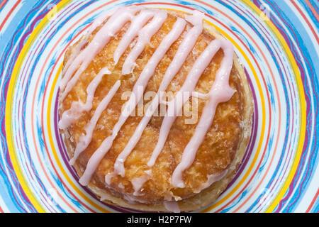 M & S Himbeere Yum Yums iced Donut auf bunten Teller