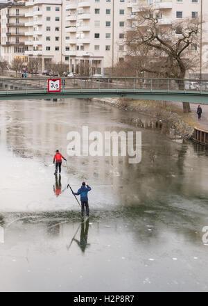Skaten auf dünnem Eis, Stockholm Stadtzentrum - paar fotografieren, wie sie auf einem Kanal auf mit was aussieht - Stockfoto