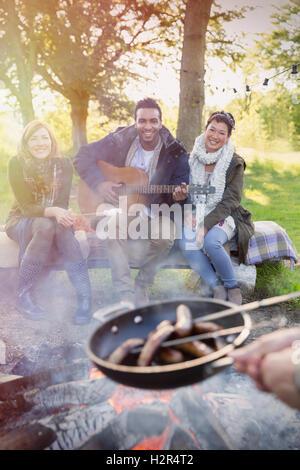 Freunde mit Kochen Hotdogs über Lagerfeuer Gitarre - Stockfoto