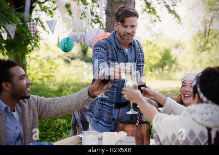 Freunde, die Weingläser an Gartenparty Tisch Toasten - Stockfoto