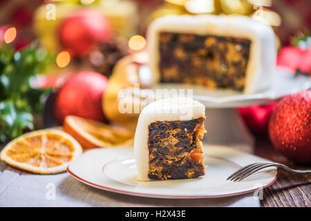 Slicing Weihnachten traditionelle festliche Obstkuchen, Weihnachtsschmuck und Dekorationen - Stockfoto