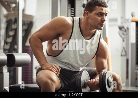 Muskuläre hart arbeitenden Menschen halten eine Kurzhantel - Stockfoto