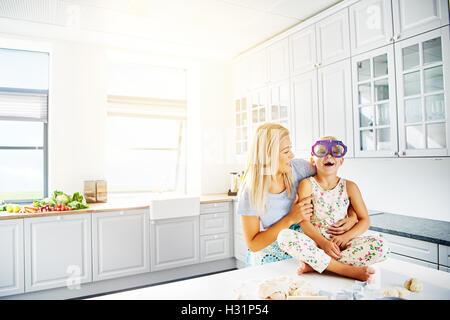 Liebenswerte Mutter und Tochter spielen zusammen in der Küche mit hellen weißen Schränke und Fenster. Textfreiraum - Stockfoto