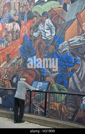 Anwohner, lesen Sie die Informationen über die Schlacht von Kabel St. Wandgemälde von Kabel St. in East London, - Stockfoto