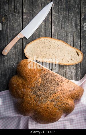 In Scheiben geschnitten Brot auf alten Holztisch. Ansicht von oben. - Stockfoto