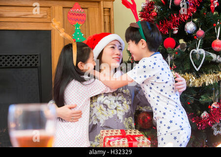 chinesische Familie an Weihnachten. Einen kleinen Jungen und Mädchen sind Gicing ihre Mutter kuscheln auf Weihnachten. - Stockfoto