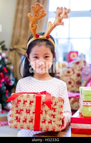 Niedlichen chinesischen Mädchen festliche Geweihe tragen. Sie ist ein Geschenk hochhalten und mit einem frechen - Stockfoto