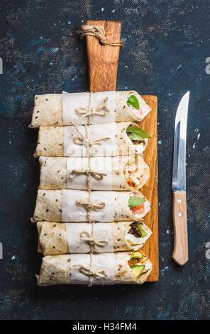 Tortilla wraps mit verschiedenen Füllungen auf grauem Beton dunkel - Stockfoto