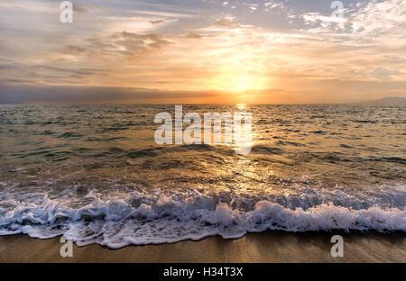 Sonnenuntergang Meer ist eine Welle ans Ufer Rollen, als die Sonne am Horizont Meer untergeht. - Stockfoto