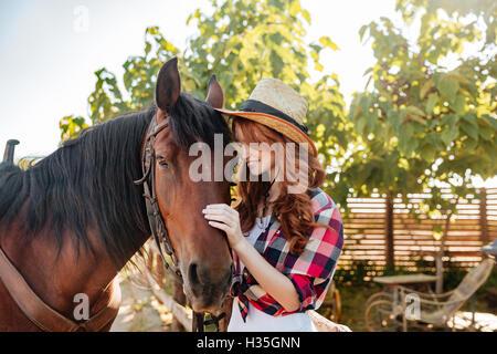 Glücklich zärtliche junge Frau Cowgirl Hut Ruf mit ihrem Pferd auf der ranch - Stockfoto