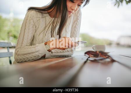 Frau Textmitteilung auf smart Phone in einem Café zu schreiben. Foto von junge Frau sitzt an einem Tisch mit Handy. - Stockfoto