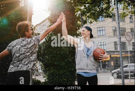 Zwei junge Freunde geben hohe fünf nach einem Spiel Streetball. Teenager Basketball-Spieler nach einem Spiel zu - Stockfoto