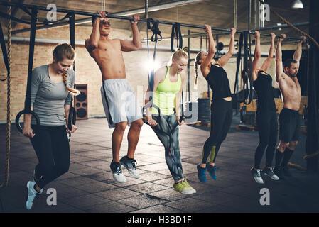 Gruppe von sechs jungen und starken männlichen und weiblichen Erwachsenen tun Chin ups mit Bar und Gurte im Cross - Stockfoto