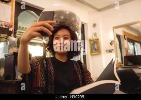 Stilvolle Frau, die eine Selfie sitzen unter einem Haartrockner - Stockfoto