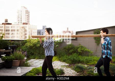Seitenansicht des Paares tragen Holzbrett während des Gehens auf Terrasse - Stockfoto