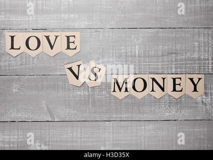 Liebe gegen Geld Papier Buchstaben Symbol Motivation zu unterschreiben auf Holzbrett - Stockfoto