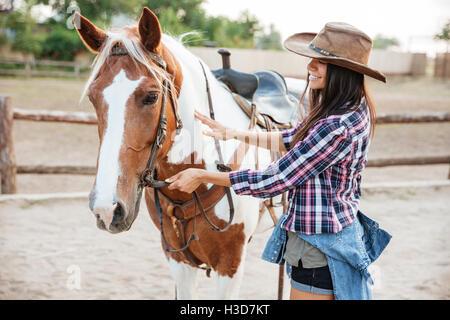 Glücklich schönen jungen Frau Cowgirl kümmert sich um ihr Pferd auf der ranch - Stockfoto