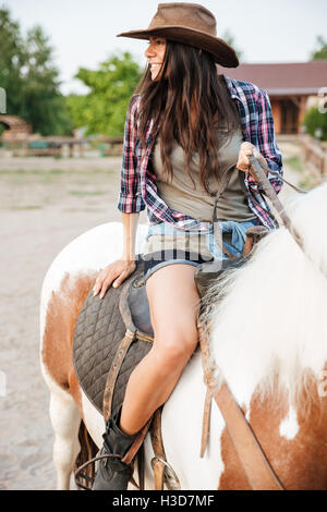 Porträt von glücklich schönen jungen Frau Cowgirl Reiten auf der ranch - Stockfoto