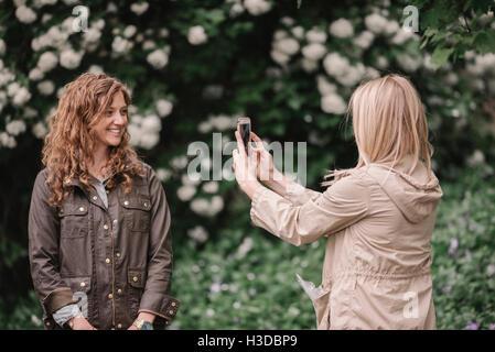 Eine Frau, die ein Foto mit einem Smartphone ihres Begleiters auf einem Feldweg. - Stockfoto