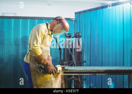 Männliche Schweißer arbeiten an einem Stück Metall - Stockfoto