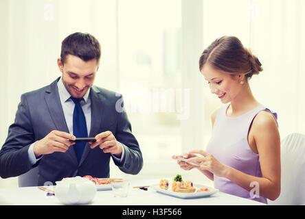 lächelnde paar mit Sushi und smartphones - Stockfoto