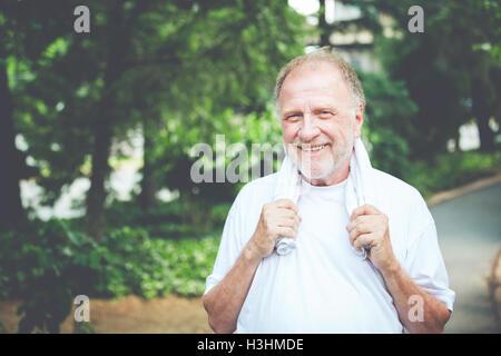 Closeup Kopfschuss Bildniss glücklich senior reifer Mann, greifen Handtuch um Hals, isoliert grüne Bäume Laub Background. - Stockfoto
