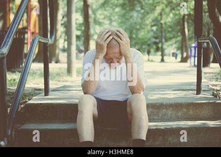 Closeup Portrait, senior reifer Mann in schwarzen Hosen und weißen Hemd, sitzen draußen auf Schritte, Hände auf - Stockfoto