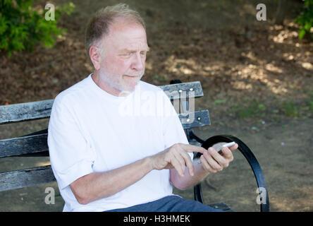 Closeup Portrait von Fett älterer Mann im weißen Hemd, schielen, Überprüfung Smartphone, SMS, sitzend auf einer - Stockfoto