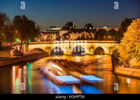 Pont Neuf Brücke beleuchtet und Seineufer in der Dämmerung mit Citylights und Touristenboot. Ile De La Cite, Paris, - Stockfoto