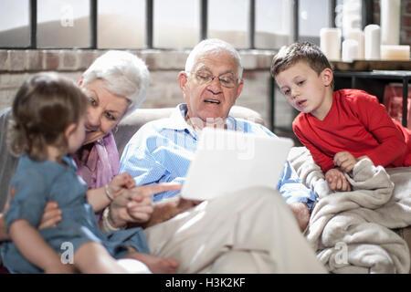 Großeltern mit Enkeln, mit digital-Tablette zu Hause spielen - Stockfoto