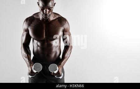 Schuss von muskulösen jungen afrikanischen Mann mit Hanteln trainieren. Passen Sie schwarze Männermodel mit Hanteln - Stockfoto