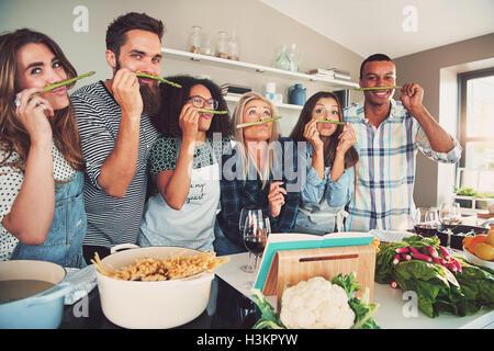 Gruppe von sechs verschiedenen albern Erwachsene schnüffeln Spargel Stiele in Küche. Schüssel mit Nudeln und Gemüse - Stockfoto