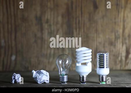 Lampe und zerknittertes Papier auf Holz Hintergrund - Stockfoto