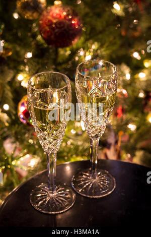 Ein Satz von zwei Sektgläser gefüllt mit Champagner ruht auf einem Tisch vor einem Weihnachtsbaum. - Stockfoto