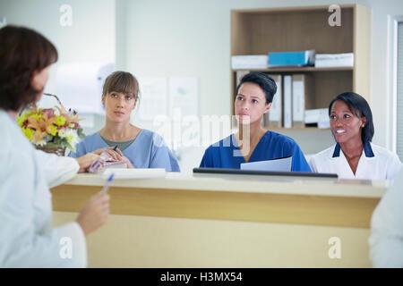Ärztin, die Diskussion mit Krankenschwestern an Krankenschwestern Station im Krankenhaus - Stockfoto