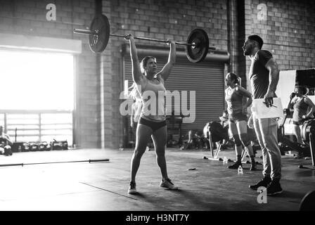 Trainer beobachten Kreuz Ausbildung Sportler heben Langhantel im Fitness-Studio - Stockfoto