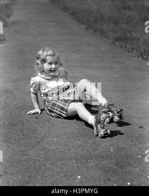 1940ER JAHRE MÄDCHEN SITZEN AUF BÜRGERSTEIG TRAGEN METALL ROLLSCHUHE HERUNTERFALLEN - Stockfoto